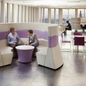 A man and a woman having an informal meeting in a office pod