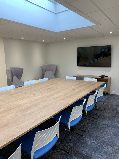 Rectangular meeting table and chairs in a room with a wall mounted screen