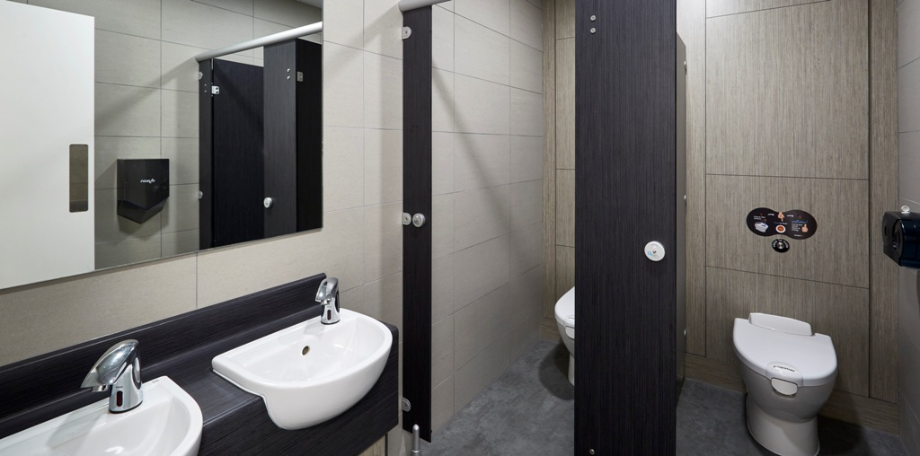 staff washroom containing 2 toilet cubicles with self-flush and 2 hand basins