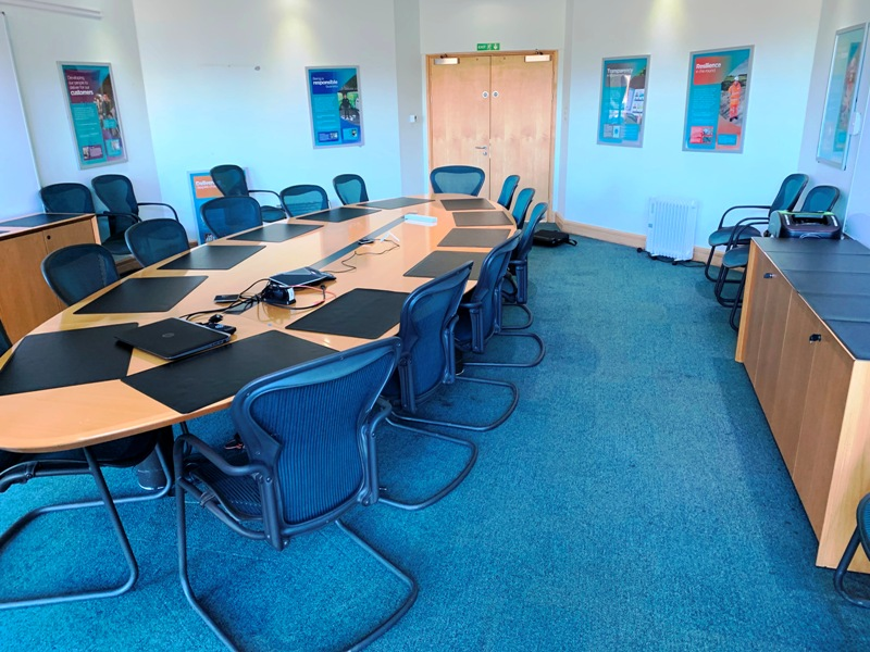 Oval boardroom table and chairs in a room with blue carpet