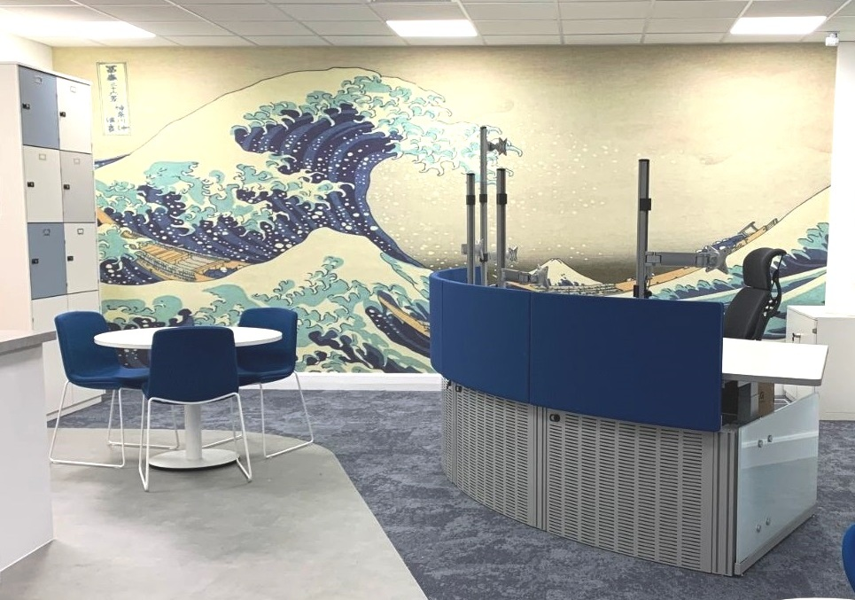 Reception desk white table and chairs with a wall featuring a sea waves design