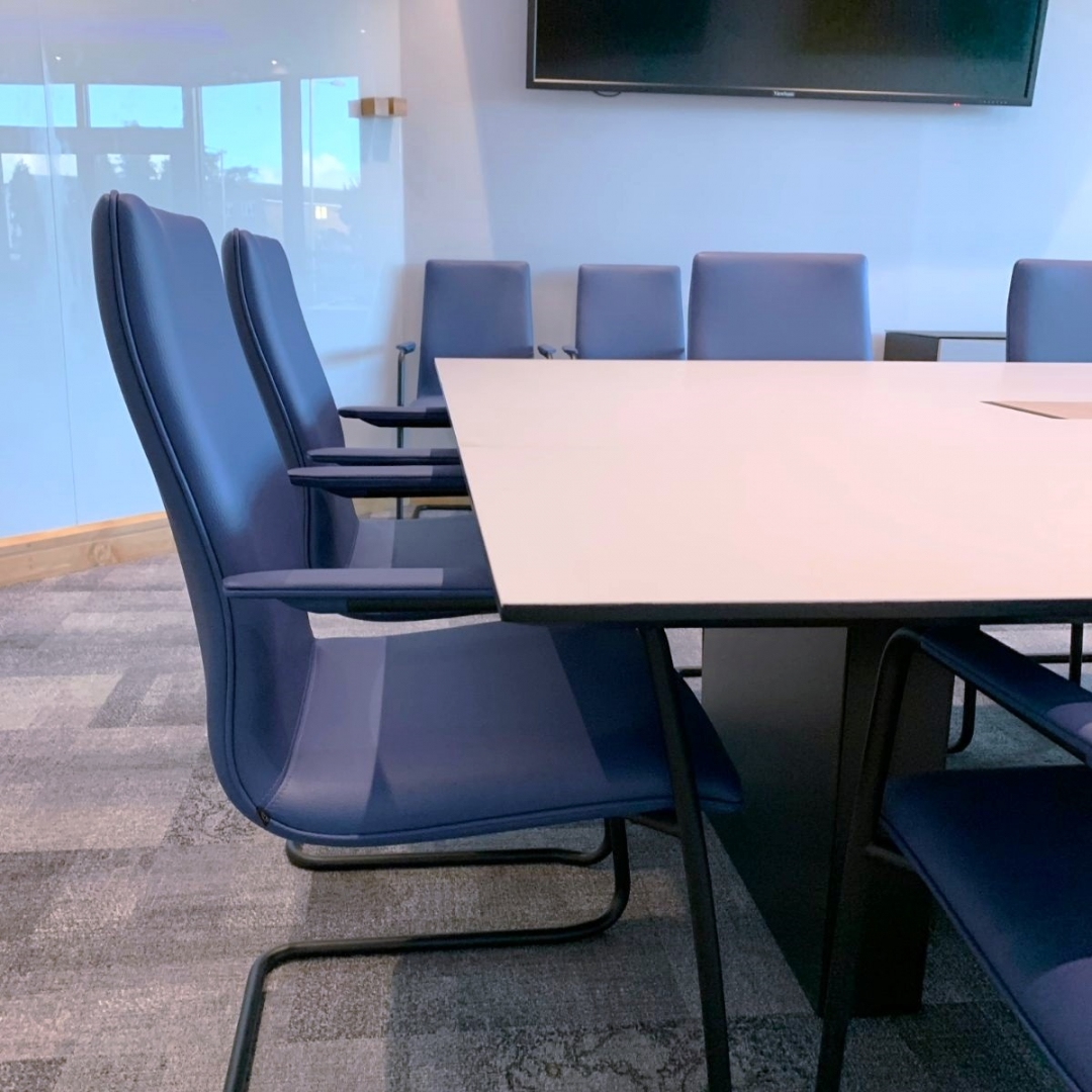 Blue chairs around a boardroom table