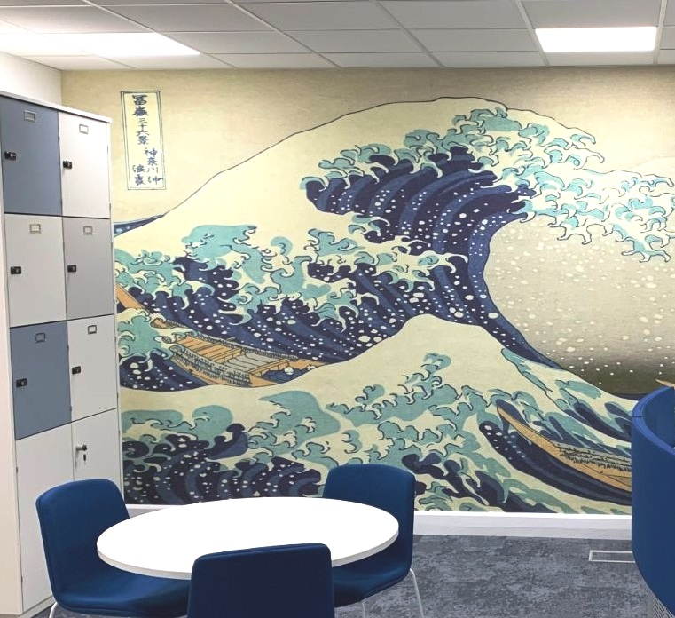Wave design feature wall in a room with lockers and a circular table